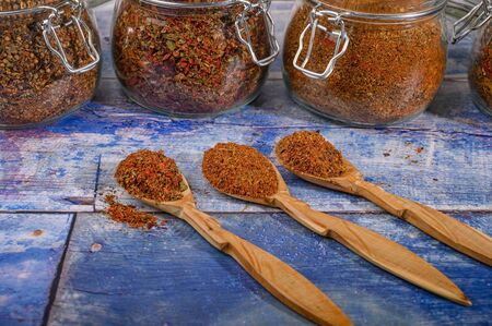 Fragrant spices in wooden spoons and glass jars on the table