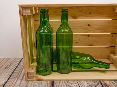 Empty wine bottles in a wooden box on the table. Home winemaking