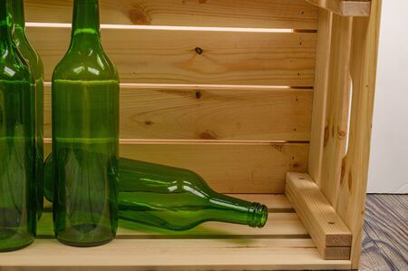 Empty wine bottles in a wooden box on the table. Home winemaking.