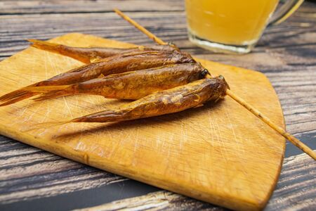 Dried mullet on a wooden Board with a mug of beer on the table. Fish and seafood cuisine. Tasty snack
