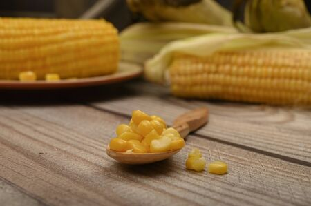Grains of sweet corn on a wooden spoon on a wooden table, in the background boiled corn and untreated ears of corn. Fitness diet. Healthy diet. For a sweet treat. Close up. Selective focus Stock Photo
