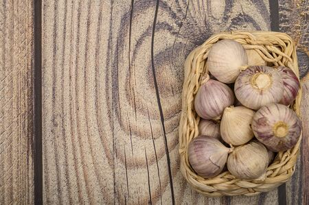 A few heads of young garlic in a wicker basket on a wooden background. Autumn harvest. Modern agriculture. Close up