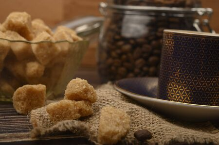 Pieces of brown sugar in a sugar bowl, a Cup of coffee, coffee beans on a wooden background. Close up
