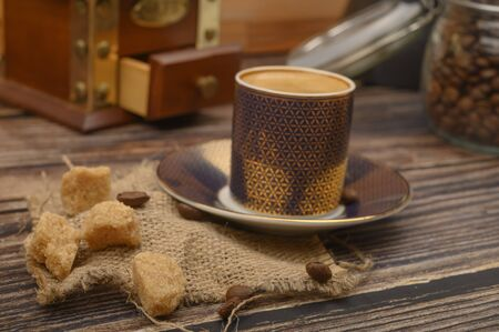 A Cup of coffee, pieces of brown sugar in a sugar bowl, coffee beans in a glass jar, a coffee grinder on a wooden background. Close up