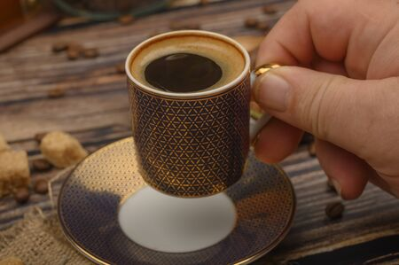 The girls hand holds a Cup of coffee over a wooden table with brown sugar and coffee beans