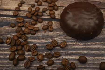 Marshmallow in chocolate and coffee beans on wooden background. Close up