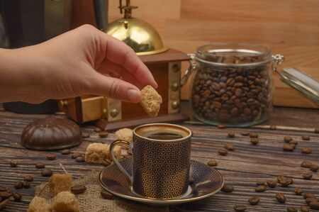 Hand girl puts a piece of brown sugar in a Cup of coffee, coffee beans, brown sugar, coffee grinder on a wooden background