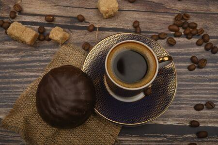 A Cup of coffee, marshmallows in chocolate, coffee beans, brown sugar on a wooden background. Close up Stockfoto