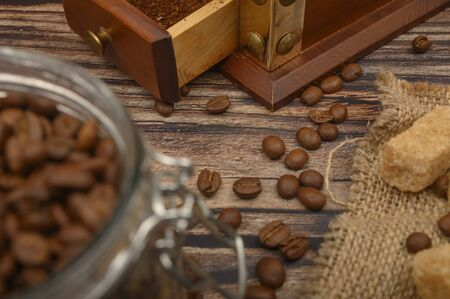 Coffee beans in a glass jar, coffee grinder, pieces of brown sugar on a wooden background. Close up Imagens