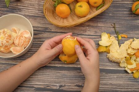 The girls hands are cleaning tangerine, tangerines on a twig with green leaves, peeled tangerines in a ceramic dish, tangerine peel on a wooden background. Autumn harvest