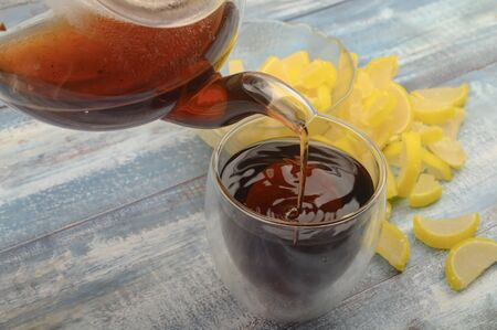 Black tea is poured from a teapot into a glass, marmalade lemon slices on a wooden background. Close up