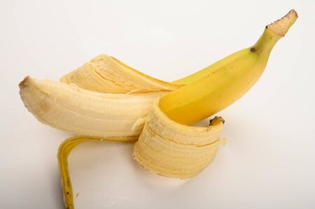One ripe yellow partially peeled banana on a white background. Close up 版權商用圖片