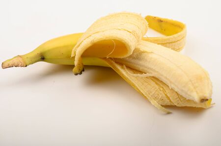 One ripe yellow partially peeled banana on a white background. Close up Banco de Imagens