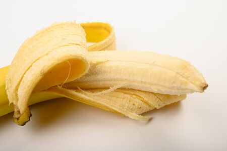One ripe yellow partially peeled banana on a white background. Close up