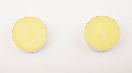 Several small colored candles in aluminum casings on a white background. Close up Imagens - 137776114