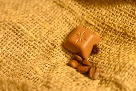 Chocolate and coffee beans on a background of rough homespun fabric. Close up Reklamní fotografie