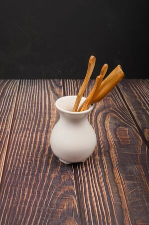 Devices for traditional Chinese tea drinking made of bamboo in a white ceramic vase in the Chinese style on a wooden background. Close up 免版税图像