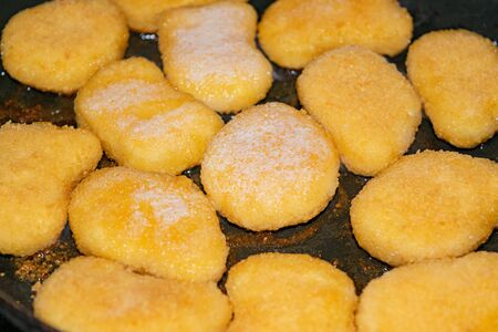 Chicken nuggets are fried in a pan. Close up