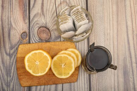 Tea in a faceted glass in a vintage Cup holder, tea bags in a glass vase and sliced lemon on a Board on a wooden background. Close up
