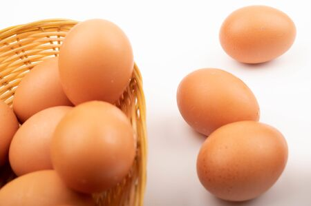 Chicken eggs in a wicker basket and scattered on a white background. Close up Standard-Bild - 141351077