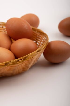 Chicken eggs in a wicker basket and scattered on a white background. Close up Standard-Bild