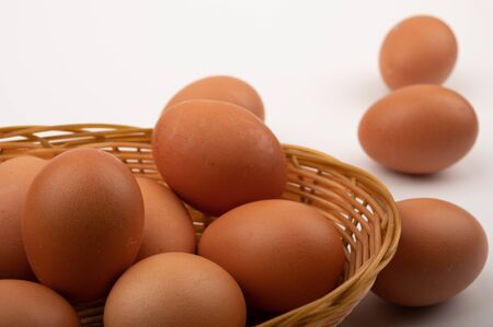 Chicken eggs in a wicker basket on a white background. Close up