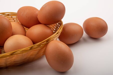 Chicken eggs in a wicker basket and eggs scattered on a white background. Country food. Close up