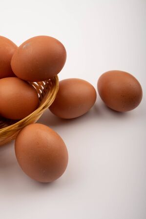 Chicken eggs in a wicker basket and eggs scattered on a white background. Close up