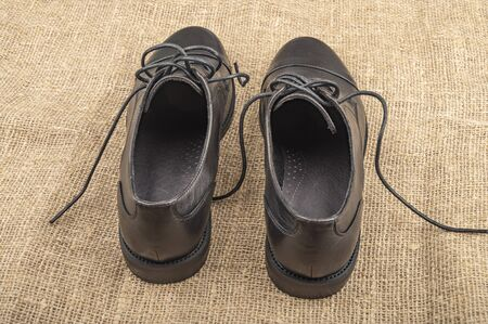A pair of black shoes with lacing on the background of textured fabric. Close up