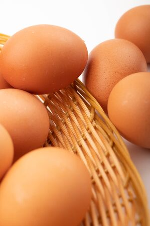 Chicken eggs in a wicker basket and scattered eggs on a white background. Close up
