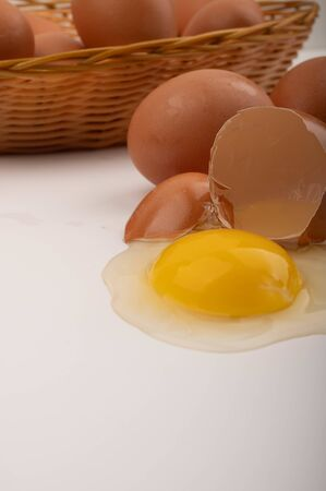 A broken chicken egg, chicken eggs in a wicker basket and chicken eggs scattered on a white background. Close up
