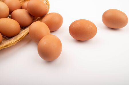 Chicken eggs in a wicker basket and scattered eggs on a white background. Close up Standard-Bild - 143009631