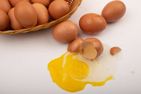 Broken chicken egg, loose chicken eggs and chicken eggs in a wicker basket on a white background. Close up
