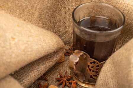 A faceted glass of tea in a vintage Cup holder and a star anise on a background of rough homespun fabric. Close up