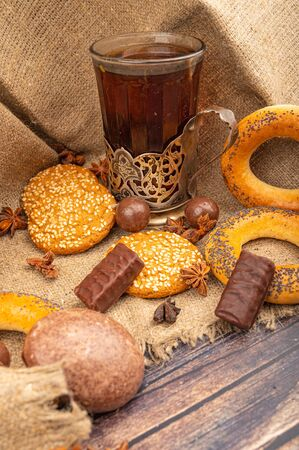 A faceted glass of tea in a vintage Cup holder, chocolate cakes, cookies, bagels and chocolate pieces on a wooden background. Close up