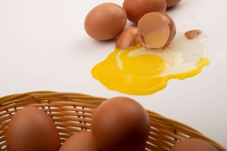 Chicken eggs in a wicker basket, broken chicken egg and chicken eggs scattered on a white background background. Close up