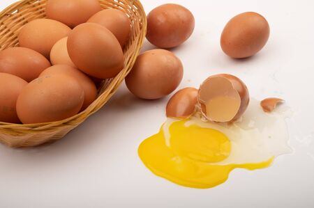 Chicken eggs in a wicker basket, scattered chicken eggs and a broken chicken egg on a white background. Close up