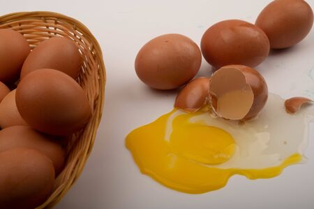Chicken eggs in a wicker basket, a broken chicken egg and scattered eggs on a white background. Close up