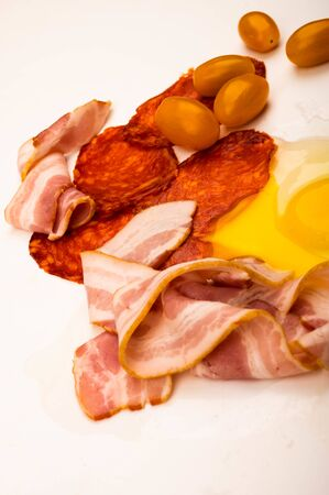 A broken chicken egg without a shell, slices of sausage and bacon and tomatoes on a white background. Close up