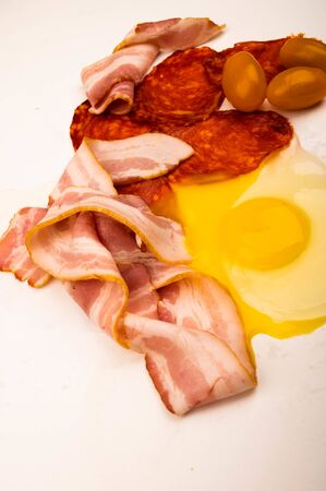 A broken chicken egg without a shell, slices of sausage and bacon and tomatoes on a white background. Close up Foto de archivo