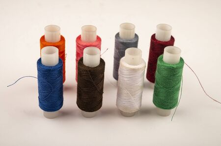 Several reels of multicolored sewing thread on a white background. Close up