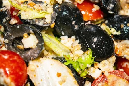Vegetable salad with cheese. Fitness salad with tomatoes, onions, olives, lettuce and cheese. Surface texture. Close up Stock Photo