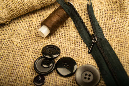 Buttons of different sizes, a spool of thread and a zipper on a burlap with a rough texture. Close up