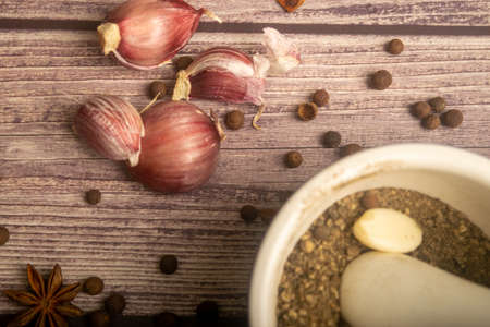 Allspice in a ceramic mortar and scattered garlic cloves, star anise and allspice on a wooden table. Close up Banco de Imagens