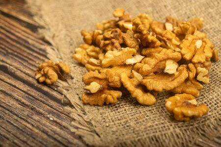 Peeled walnuts in bulk on a wooden table covered with rough-textured burlap. Healthy diet. Fitness diet. Close up Standard-Bild