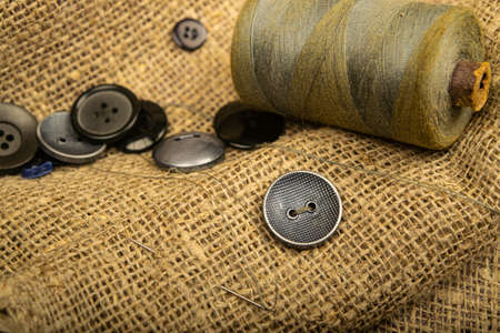 Different buttons and a spool of thread on the burlap with a rough texture. Close up Archivio Fotografico