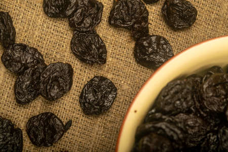 Dried prunes in a ceramic bowl and dried prunes scattered on a background of coarse-textured burlap. Close up