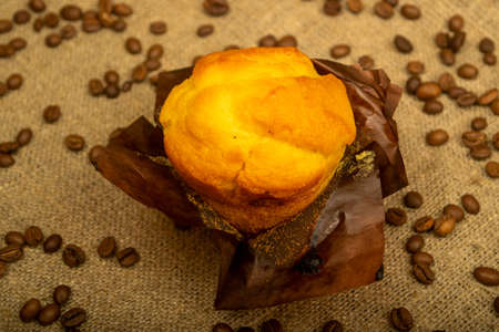 Fresh cupcake and coffee beans on a homespun fabric with a rough texture. Close up
