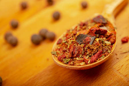 Different ground spices in a wooden spoon on a wooden background. Close up Standard-Bild
