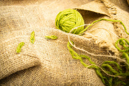 A ball of green thread on rough-textured burlap. Close up